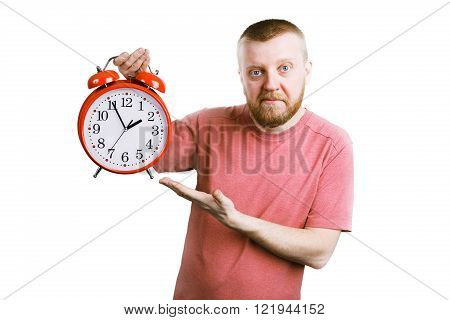 Bearded man with a red alarm clock in his hand