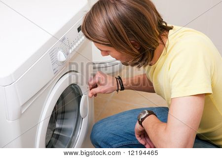 Man washing clothes using a washer