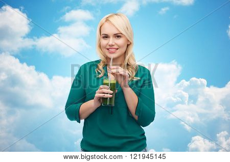 healthy eating, vegetarian food, diet, detox and people concept - smiling young woman drinking green vegetable juice or smoothie from glass over blue sky and clouds background