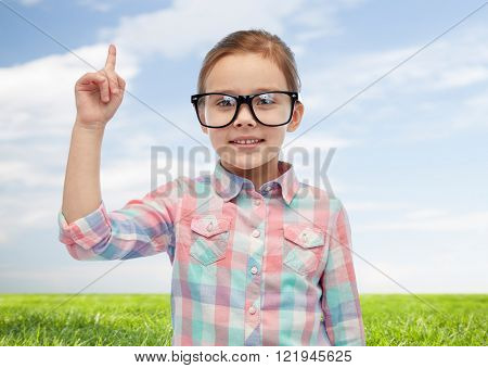 childhood, school, education, vision and people concept - happy little girl in eyeglasses pointing finger up over blue sky and green field background