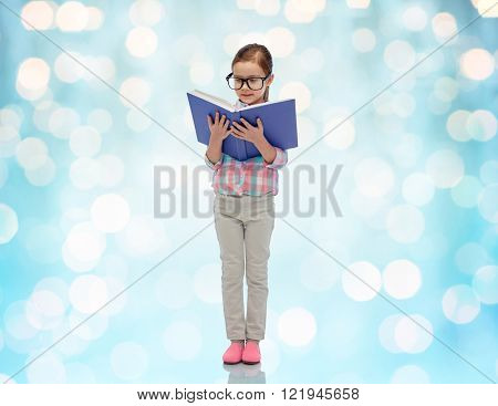 childhood, school, education, vision and people concept - happy little girl in eyeglasses reading book over blue holidays lights background