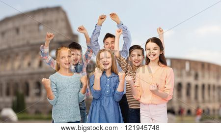 childhood, travel, tourism, gesture and people concept - happy children friends raising fists and celebrating victory over coliseum in rome