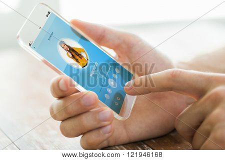 technology, modern gadgets and people concept - close up of male hand holding transparent smartphone with music player on screen