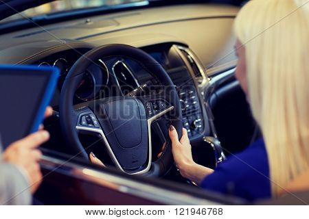 auto business, car sale, technology and people concept - close up of woman and car dealer hands with tablet pc computer in auto show or salon