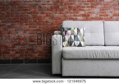 Grey sofa against brick wall in the room