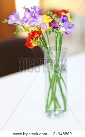 Beautiful bouquet of colorful freesias flowers on wooden table at living room