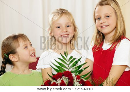 Three children - all girls - waiting with a bunch of roses for their mother, to give the flowers for birthday or mothers's day