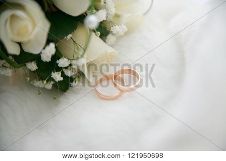 Wedding bouquet and rings on the background of fur