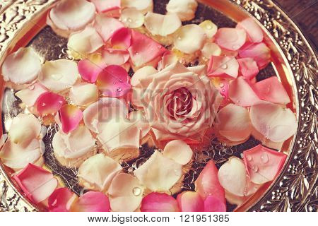 Pink and white rose petals in silver bowl, close up