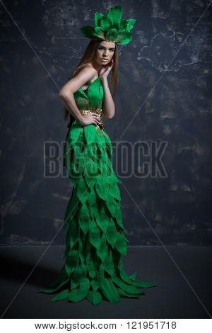 Beautiful sexy young girl , woman,  lady, model  posing in long paper green dress in  fashion photo studio, grey background