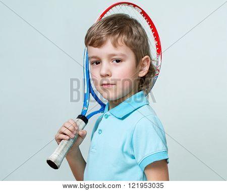 Portrait Of A Cute Little Boy Holding A Tennis  Racquet