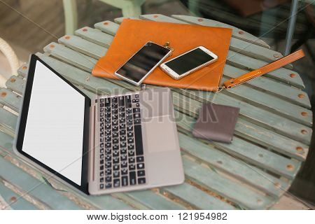 Laptop smartphones wallets and leather bag in outdoor working space