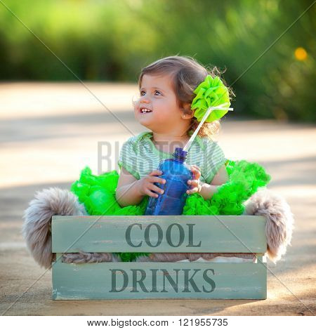cute summer girl child sitting in box with bottle of water