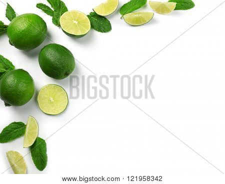 Colorful green limes sliced and halved with mint sprigs isolated on a white background, top view