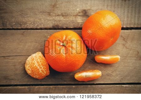 Unpeeled tangerines  with slices on the wooden table, top view