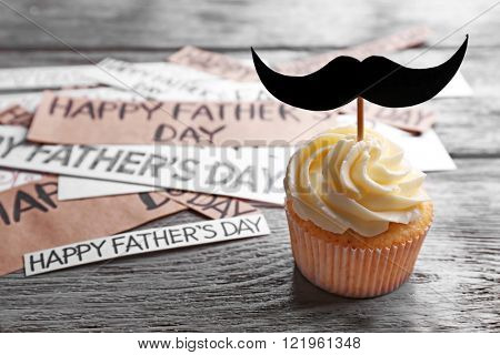 Happy fathers day special cupcake with mustache on wooden table