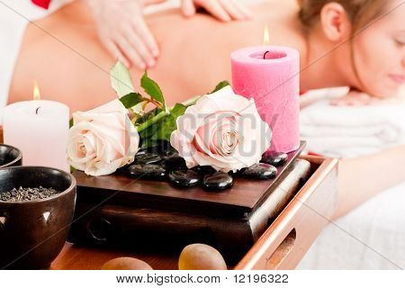 Spa - accessories in foreground, woman enjoying a back massage in the background (Focus on foreground!)
