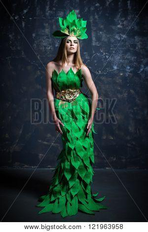 Beautiful sexy young girl woman lady model posing in long paper green dress in fashion photo studio grey background