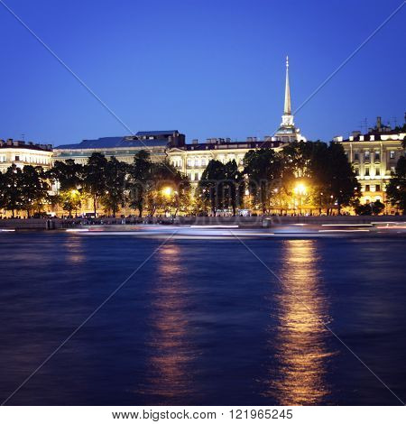 White Nights in Saint Petersburg. River bank and Spire of Admiralty building. Aged photo. Neva river with moving boats. Retro filter. Summer night. St. Petersburg Russia.