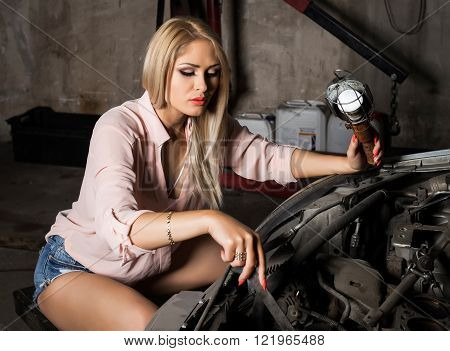 Beautiful young woman repairing a car in a auto service.