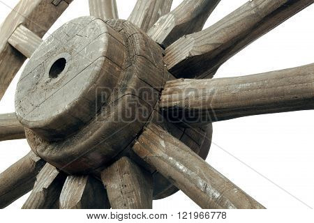 Upward closeup front view of spokes and hub of vintage weathered wooden wagon wheel on white