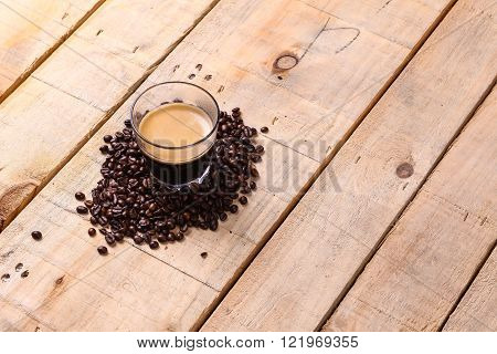 Tumbler glass with fresh coffee surrounded by roasted coffee beans over a grunge wooden background