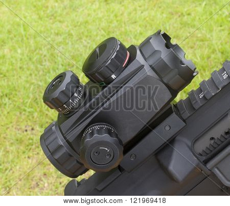 Very short scope mounted on a rifle with a green background