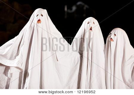 Three very, very scary spooks - kids dressed as ghosts - on Halloween or for carnival or a costume party