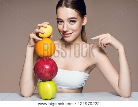 Young woman with fruits mix, healthy life concept, photo of attractive girl indicates on fruit pyramid / portrait of girl with fruits mix on the table over beige background