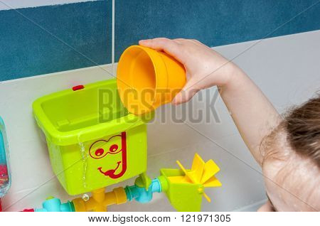 Little girl is taking a bath playing with a toy watering-pot