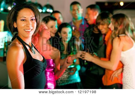 Group of friends - men and women of different ethnicity - having fun in a disco or nightclub drinking; beautiful colored woman in front