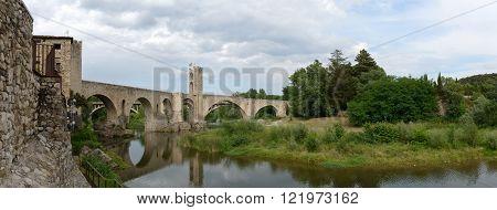 Scenic panoramic view of ancient bridge across Fluvia River in medieval town Besalu Catalonia Spain.