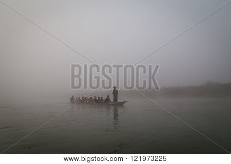 Canoe on river in morning mist, Chitwan National Park, Nepal