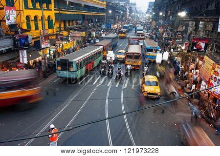 KOLKATA, INDIA - JAN 17: People and cars blurred in motion on the busy street of the asian metropolis on January 17, 2013 in Kolkata, India. Kolkata has a density of 814.80 vehicles per km road length