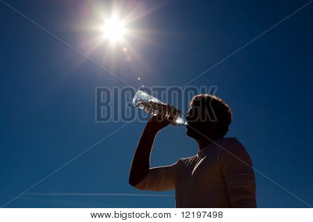 Sportive man drinking water from a bottle against a blue sky background under a hot sun