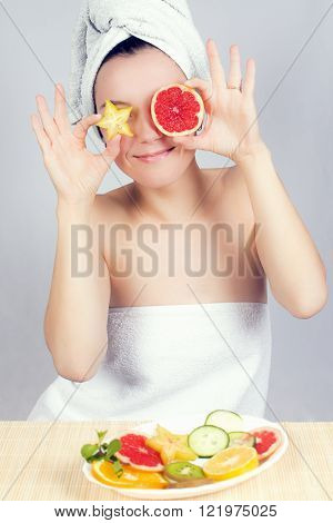 Young woman holds slices of carambola and red grapefruit like her eyes.