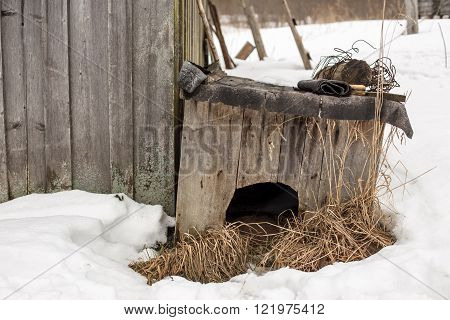 old wooden doghouse is about a barn in the village during the snowy winter