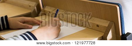 Close-up of female student's hand writing a final exam at university