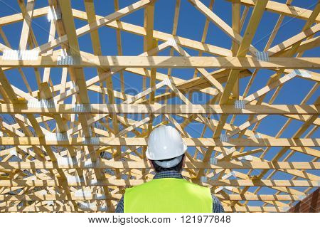 Construction Worker Looking At The Roof Of A House Under Construction, With A Clear Blue Sky In The
