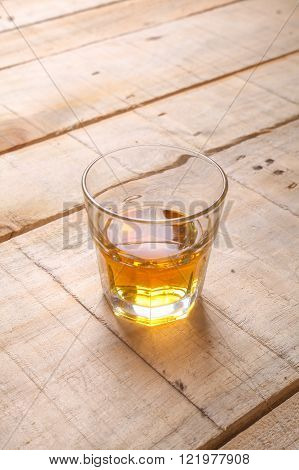 Tumbler glass with whiskey on a grunge wooden table