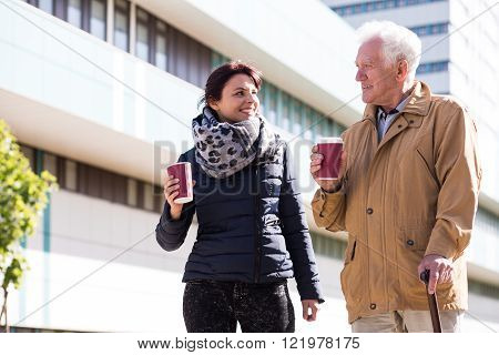 Picture of senior male with walking stick and caring woman