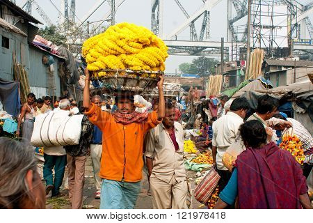 KOLKATA, INDIA - JAN 13: Worker with a cart on the head rush on the crowded Mullik Ghat Flower Market on January 13, 2013 in Kolkata. The market is 125 years old. 2000 sellers work in it every day.