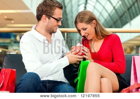 Couple - man and woman - in a shopping mall with colorful bags, he has bought a present for his wife or girlfriend, she is surprised