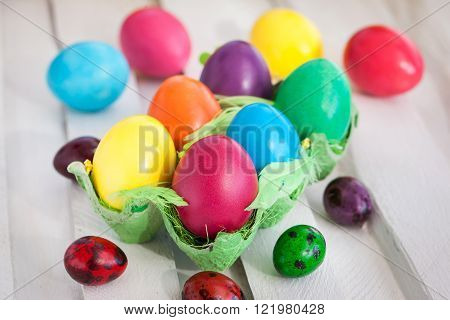 Colorful painted Easter eggs in a carton on white background