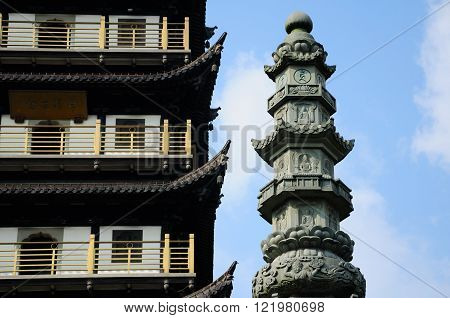 Zhenru Temple Pagoda and a Buddhist prayer pillar with prayers and Buddhist gods carved on the stone located in Shanghai China.