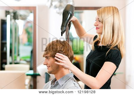 Man at the hairdresser, she has finished the cut and is drying his hair with a blow dryer