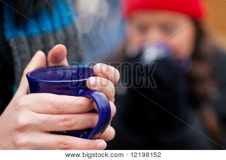 Menschen auf ein Weihnachtsfest Markt trinken Punsch oder scharf gewürzt Wein, es ist kalt, und sie haben das Bedürfnis, w