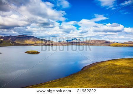 Cool blue water of the lake among the yellow tundra. The magic of summer in Iceland