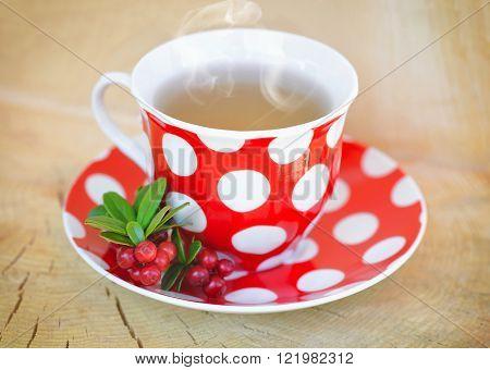 Cowberry (Vaccinium vitis-idaea) tea on a wooden table