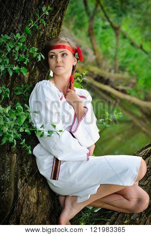 Beautiful young girl in folk costume outdors